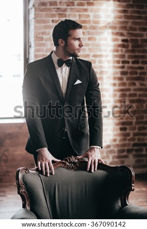 Confidence and contemplation. Thoughtful young handsome man in full suit and bow tie leaning at the chair and looking away while standing in loft interior - stock photo