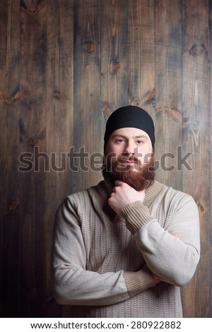 Confidence and manhood. Handsome young bearded man looking at camera on the wooden background - stock photo
