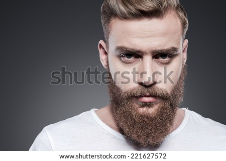 Confidence and masculinity. Portrait of handsome young bearded man looking at camera while standing against grey background - stock photo