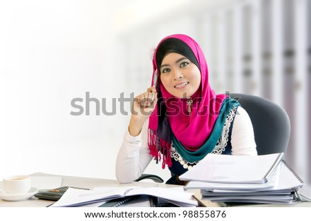 Confidence and smiles of young busy muslim businesswoman while working - stock photo