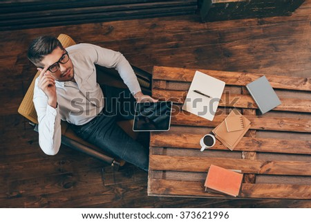 Confidence and success. Top view of handsome young man holding touchpad and looking at camera while sitting at his working place - stock photo