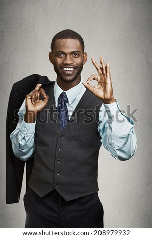 Confidence, charisma. Closeup portrait Cheerful young African man in full suit, giving Ok sign, gesture looking at camera, isolated grey wall background. Human face expression, emotion, body language - stock photo