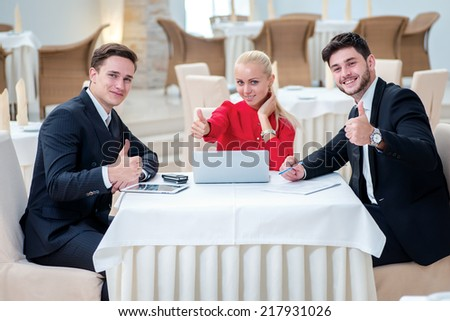 Confidence in the work Three successful businessman discussing work at a laptop. Businesspeople in formal dress sitting in the office at the table and showing thumbs up.