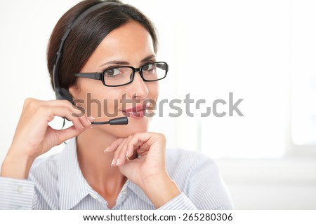 Confident adult employee with glasses speaking on headphones while cheerfully looking at you - copyspace - stock photo