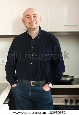 Confident adult man standing in  kitchen - stock photo