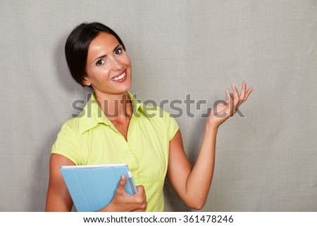 Confident adult woman carrying a tablet with left palm horizontal as showing and smiling in casual clothing while looking at camera on grey texture background - stock photo