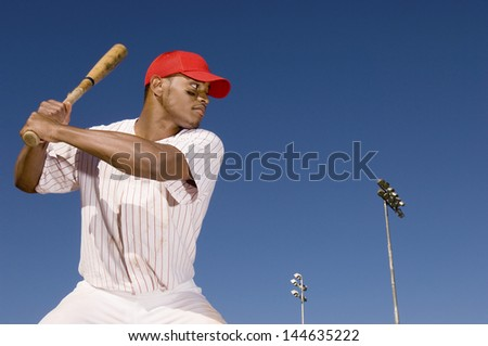 Confident African American baseball batter waiting to strike the ball - stock photo