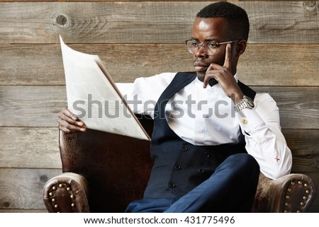 Confident African CEO in formal suit and glasses reading financial newspaper with concentrated expression, sitting in leather armchair against wooden wall in the morning. Business and success concept - stock photo
