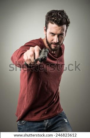 Confident aggressive man holding a gun, cool attitude - stock photo