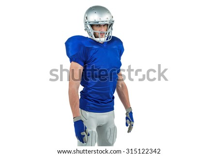 Confident American football player standing against white background