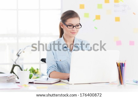 Confident and creative. Cheerful young woman working on laptop and smiling - stock photo