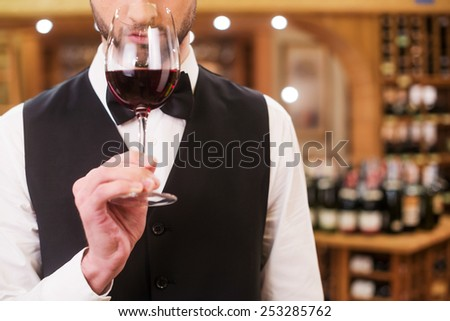 Confident and experienced sommelier. Close-up of confident young man in waistcoat and bow tie holding wine glass with red wine and smelling it - stock photo