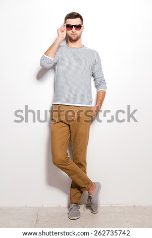 Confident and handsome. Full length of handsome young man adjusting his sunglasses while leaning at the white wall  - stock photo