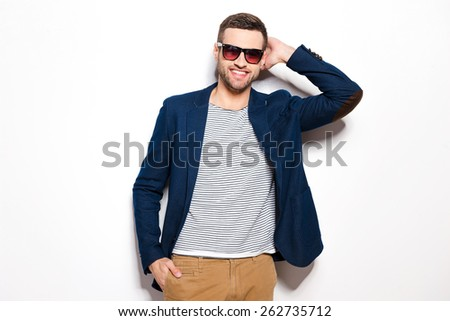 Confident and handsome. Handsome young man in sunglasses holding hand behind head and smiling while standing against white background  - stock photo
