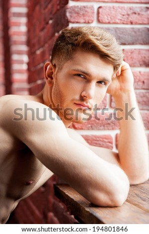 Confident and handsome. Handsome young shirtless man looking at camera while leaning at the window sill  - stock photo