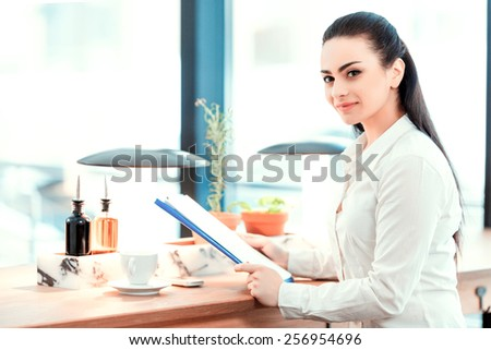 Confident and successful business lady. Side view of beautiful young woman in formalwear looking at clipboard with analytics while sitting at the restaurant - stock photo