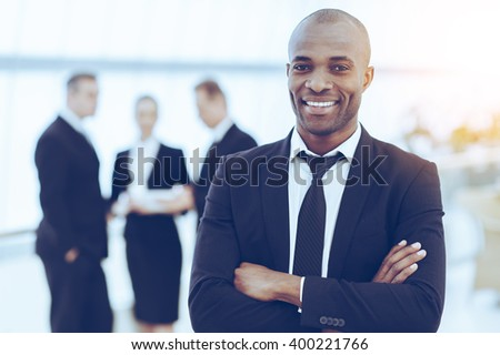 Confident and successful businessman. Cheerful young African man in formalwear keeping arms crossed and smiling while his colleagues standing on background - stock photo