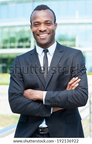 Confident and successful businessman. Handsome young African man in full suit keeping arms crossed and looking at camera while standing outdoors - stock photo