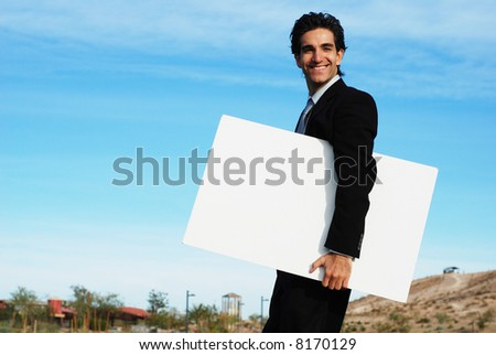confident and successful businessman is holding a blank board
