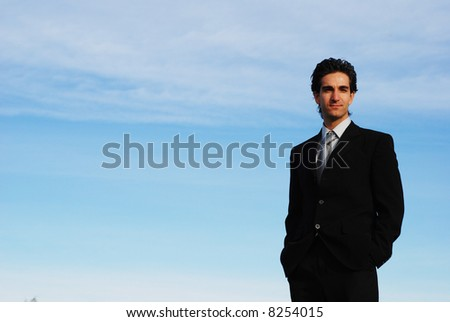 confident and successful businessman is posing against the sky