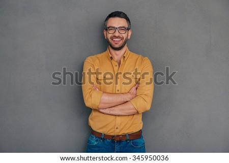 Confident and successful. Confident mature man holding hand on chin and looking at camera with smile while standing against grey background - stock photo