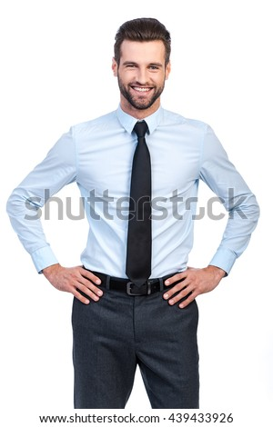 Confident and successful. Confident young handsome man in shirt and tie holding hands on hip and smiling while standing against white background  - stock photo