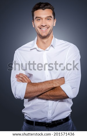 Confident and successful. Happy young man in white shirt looking at camera and keeping arms crossed while standing against grey background - stock photo