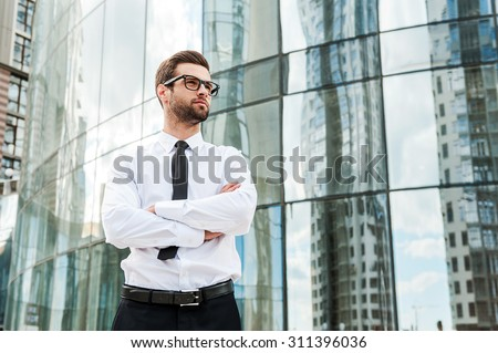 Confident and successful. Low angle view of confident young businessman keeping arms crossed and looking away while standing outdoors with office building in the background - stock photo