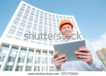 Confident architect. Handsome young man in hardhat using tablet computer while standing outdoors and against building structure. - stock photo
