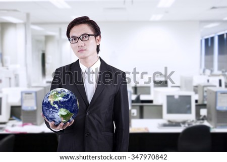Confident asian businessman holding a globe in the office - stock photo