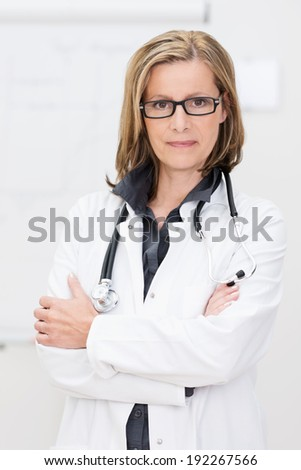 Confident attractive woman doctor standing with her arms folded wearing glasses looking at the camera with a serious expression - stock photo