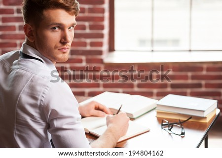 Confident author. Handsome young man in shirt and tie writing something in note pad and looking over shoulder while sitting at his working place  - stock photo