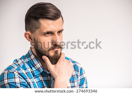 Confident, bearded man is thinking about something. Grey background. - stock photo