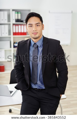 Confident bearded young Asian businessman in black blazer jacket and blue shirt with tie leaning back on table in front of bookshelf at office - stock photo