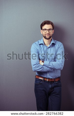 Confident bearded young man wearing brown leather belt, wristwatch, eyeglasses and blue jeans and casual shirt while standing with folded arms and leaning against a grey wall - stock photo