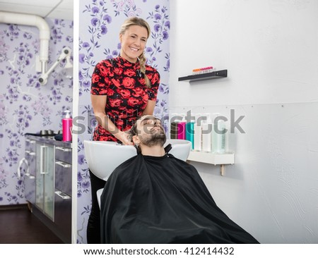 Confident Beautician Washing Male Customer's Hair - stock photo