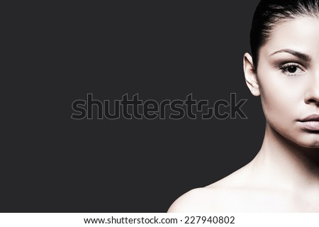 Confident beauty. Half face of shirtless young woman looking at camera while standing against grey background  - stock photo