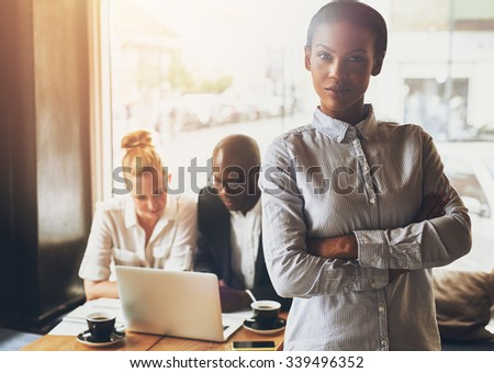 Confident black business woman standing in front of colleagues - stock photo