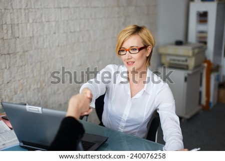 Confident blonde businesswoman greeting someone office stock photo confident blonde businesswoman greeting someone in an office m4hsunfo