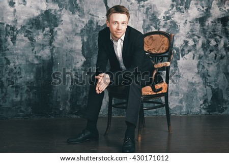 Confident blonde man in formal suit sits on an vintage chair.  Cinema colour graded.