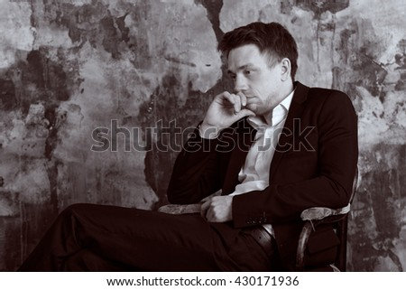 Confident blonde man in formal suit sits on an vintage chair. Vintage Black and White colour graded.