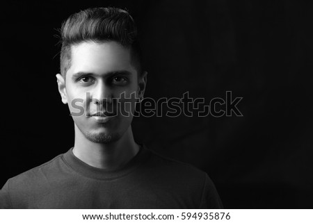 Confident boy posing against a black background shot in a studio.