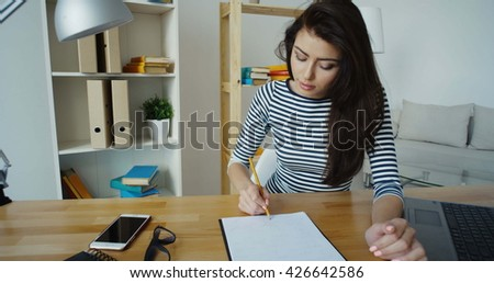 Confident brunette businesswoman in glasses taking note in a notepad at office, close-up - stock photo