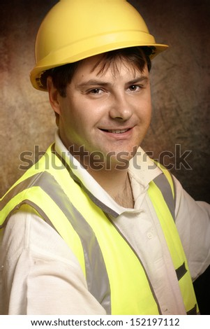 Confident builder, handyman or construction worker wearing hard hat and vest is smiling.