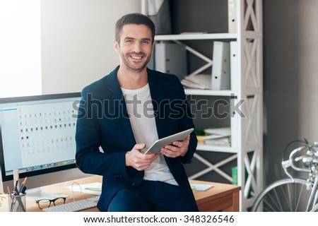 Confident business expert. Confident young man holding digital tablet and smiling while leaning at the deck in office - stock photo