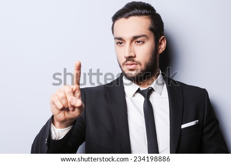 Confident business expert. Confident young man in formalwear pointing and looking at his finger while standing against grey background - stock photo