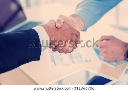 Confident business handshake. Close-up view of a handshake while two successful businessman shaking hands at the table against each in the business office in formal wear and work at a laptop. - stock photo