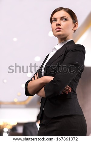 Confident business lady. Low angle view image of beautiful young woman in formalwear keeping arms crossed and looking away - stock photo