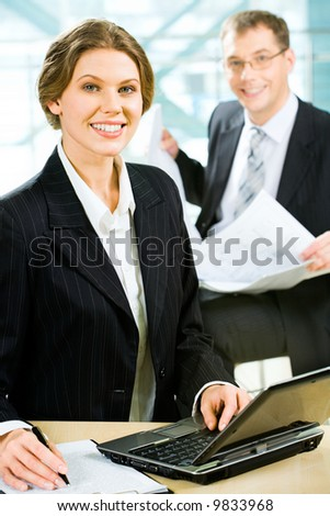 Confident business lady sitting at the table before a laptop with documents near by on the background of her business partner with business papers