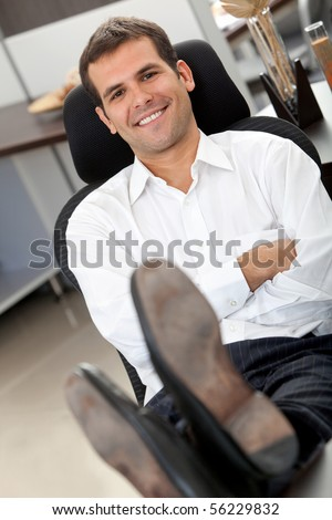 Confident business man at the office with his feet on the desk